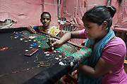 Dhaka, Bangladesh. The three girls, Rabia,18, Munni,15 and Sabia,13, work at home making saris. A factory out-let has commissioned the work. It  take s2 weeks to make a sari and they get £3 /sari each. Rabia and Munni are sister and both suffer from Rheumatic Arthritis and sitting down working 9 hours/ day seven days a week only makes their condition worse. Sabia wants to go to school but both Rabia and Muni prefer not to go out. Their disability has made them very shy, they cant walk properly and standing up Rabia is now only the size of a 10 year old. Her father says that if they were to go to school, who would then pay for their medication, not to mention the loss of income they generate...best to stay at home he says. The Stars Foundation visiting CSID.<br /> Centre for Services and Information on Disability (CSID) is a charity working for integrating disabled children into mainstream society.
