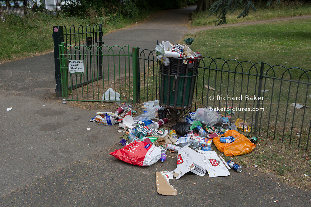 Litter overspill of beer cans and general rubbish, overspilled from a public park bin, on 23rd June 2017, Ruskin Park, south London borough of Lambeth.