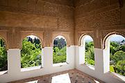 Arched decorated Moorish stone windows looking over gardens, Generalife garden, Alhambra, Granada, Spain