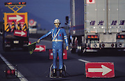 """A Japanese battery-operated robot traffic officer, """"anzen taro"""" (which means """"safety boy""""), directs traffic at a construction zone on an expensive toll road near Mt. Fuji, outside Tokyo, Japan. (Man Eating Bugs page s 30, 31)"""