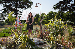 © Licensed to London News Pictures. 08/07/2013. London, UK. Journalist Claire French uses an umbrella to keep herself dry as she stands in 'The Native Shower' a garden designed by Bayley LuuTomes at the press view for the Royal Horticultural Society's Hampton Court Palace Flower Show today (08/07/2013). Photo credit: Matt Cetti-Roberts/LNP