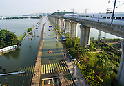 WUHAN, CHINA - JULY 09: Aerial view of residents walking on the temporary plank above the flooded road on July 9, 2016 in Wuhan, Hubei Province of China. A temporary wooden plank was built for residents over the flooded road near the Tangxun Lake. Heavy rains made the water level rise in Tangxun Lake and many roads were flooded in Wuhan. <br /> ©Exclusivepix Media