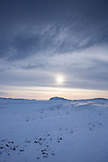 Wintry sun and cloud formation, above snow-covered glacial landscape and lava fields in South Iceland