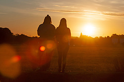 ©Licensed to London News Pictures 30/07/2020     Blackheath, UK. Two teenage girls have got up very early to watch the sunrise. Another hot weather day is expected today in the UK as a bright warm sunrise comes up over Blackheath Common this morning in London.  Photo credit: Grant Falvey/LNP