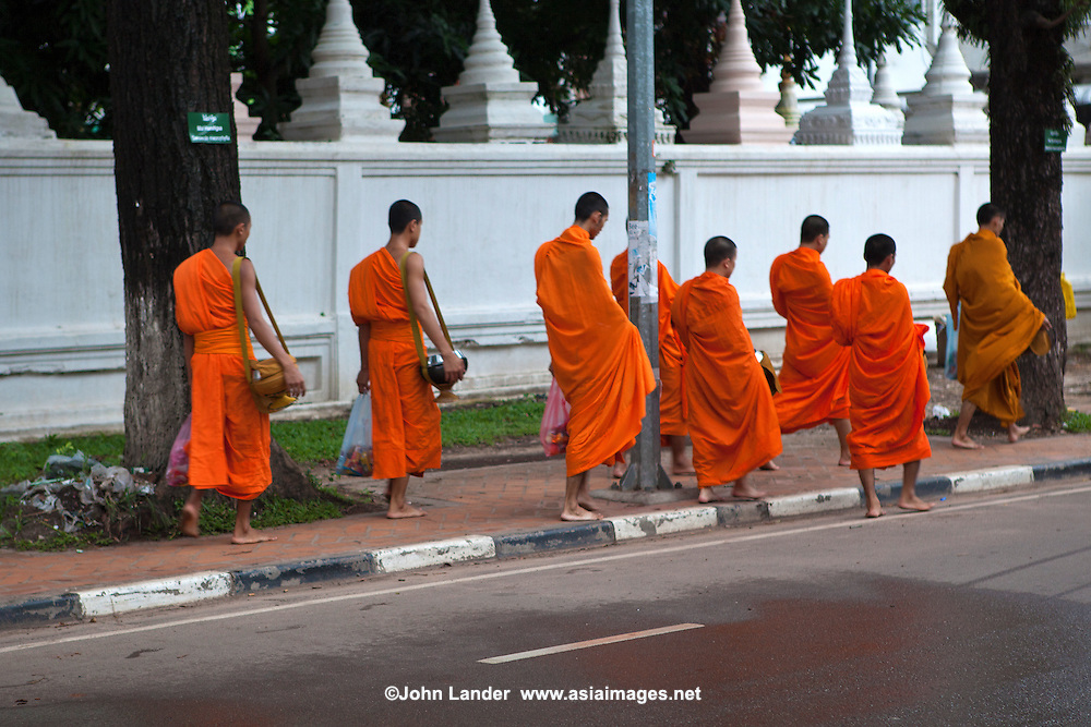 Monks Collecting Alms - the respect given by a lay Buddhist to a Buddhist monk or nun is not charity as presumed by Western eyes but it is closer to a symbolic connection to the spiritual showing humility and respect.  The presence of so many Buddhist monks is a stabilizing influence in Lao society and the act of alms giving assists in connecting lay people to the monk and what he represents.
