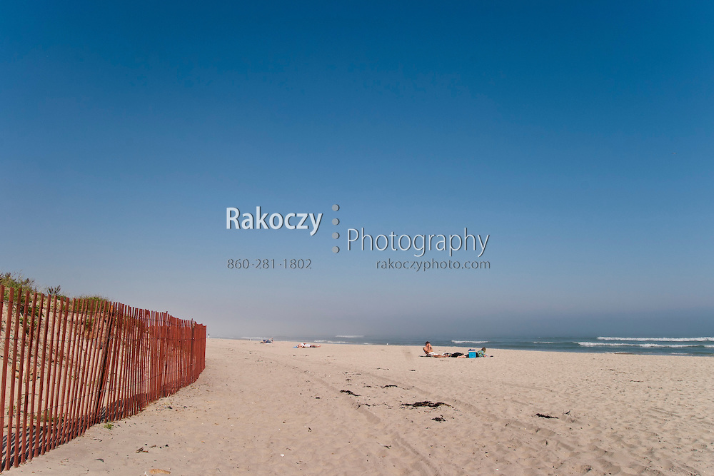A scattered few people still enjoy the warm sun and blue skies over a beach in Ogunquit, Maine.