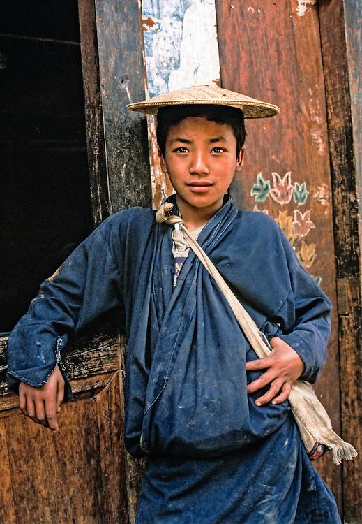 BHUTAN, PEOPLE boy wearing bamboo hat