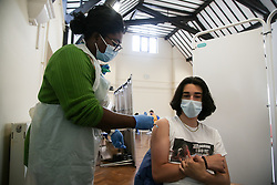© Licensed to London News Pictures. 28/06/2021.  London, UK. Vaccinator Lily administers the Pfizer Covid-19 vaccine to 24 year old Hakan Erturk in Tottenham, north London. <br /> As the new Health Secretary, Sajid Javid, prepares to update Parliament on the COVID-19 pandemic, the Prime Minister Boris Johnson, has said he expects restrictions to be eased on 19 July. The government updates come as Professor Sir Andrew Pollard of the Oxford Vaccine Group, has said that two doses of the Astra Zeneca vaccine are proving effective against the Delta variant, such that autumn boosters may not be required. Photo credit: Dinendra Haria/LNP