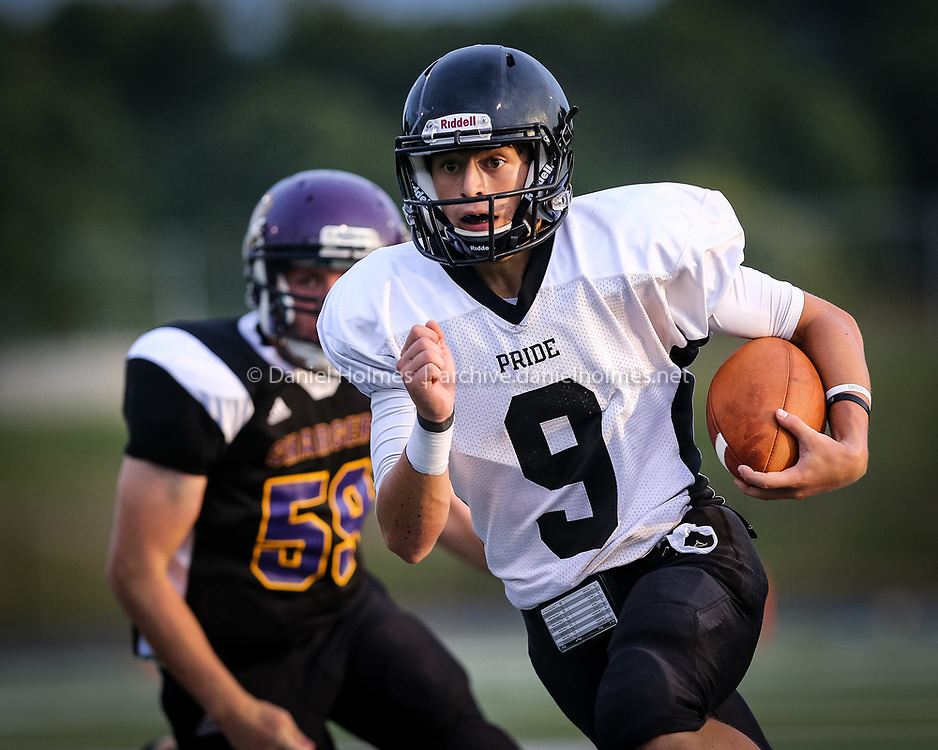 (9/6/14, BELLINGHAM, MA) Bellingham's Alec Godfrey runs the ball under pressure from the defense during the football game against Blackstone-Millville at Bellingham High School on Saturday. Daily News and Wicked Local Photo/Dan Holmes