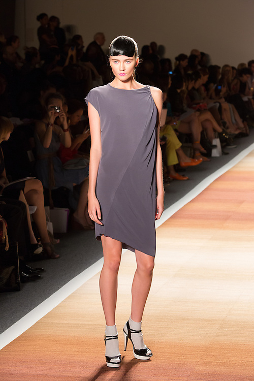 A purple-gray dress with asymmerical sleeve treatment and an asymmetrical hem.