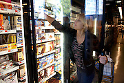 Mariel Booth, a professional model and New York University student, reaches for  Tofutti Cuties at a Whole Foods grocery store near her apartment in New York city. (From the book What I Eat: Around the World in 80 Diets.) The caloric value of her day's worth of food on a day in the month of October was 2400 kcals. She is 23 years of age; 5 feet, 9.5 inches tall; and 135 pounds. At a healthier weight than when modeling full-time, she feels good but laments that she's making much less money. MODEL RELEASED.