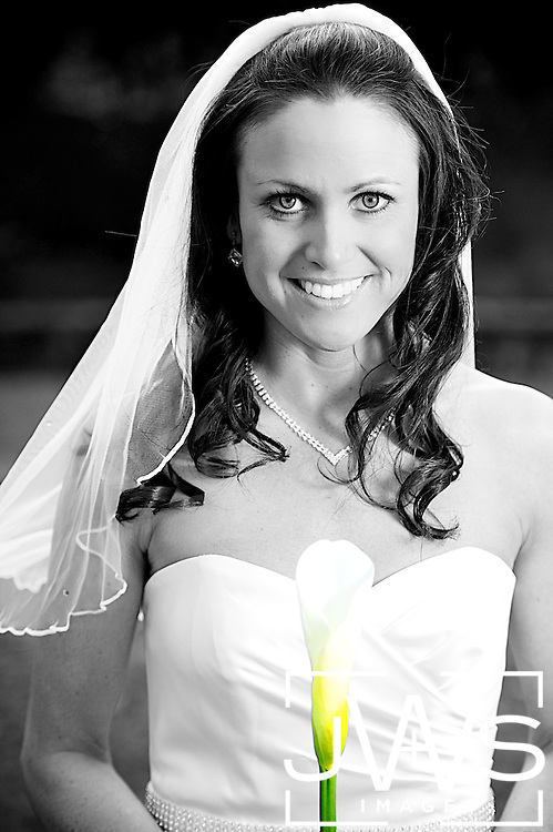 Black and white portrait of bride with colored flower
