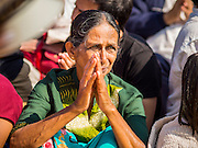 """02 JANUARY 2015 - KHLONG LUANG, PATHUM THANI, THAILAND: An Indian woman prays at Wat Phra Dhammakaya on the first day of the 4th annual Dhammachai Dhutanaga (a dhutanga is a """"wandering"""" and translated as pilgrimage). More than 1,100 monks are participating in a 450 kilometer (280 miles) long pilgrimage, which is going through six provinces in central Thailand. The purpose of the pilgrimage is to pay homage to the Buddha, preserve Buddhist culture, welcome the new year, and """"develop virtuous Buddhist youth leaders."""" Wat Phra Dhammakaya is the largest Buddhist temple in Thailand and the center of the Dhammakaya movement, a Buddhist sect founded in the 1970s.   PHOTO BY JACK KURTZ"""