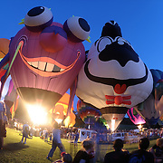 The Flying Purple People Eater (left) and Spunky the Skunk help to light up the night at the annual glow at the Bra Burn Golf Course in Dansville to help kick off the New York State Festival of Balloons on August 29, 2013.