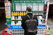 A Japanese salaryman looks at mobile telephones next to a sign advertising the ability to pay with Bitcoin in the Bic Camera store in Yurakucho, Tokyo, Japan. Friday, January 19th 2018.  Japan elevated crypto-currencies  to the same status as other forms of money in March 2016 then in April 2017 allowed businesses to use Bitcoin as a legitimate form of payment. This led to large value hikes on this digital currency. Investing and using Bitcoins continues to gain popularity in Japan despite recent drops in their trading value.