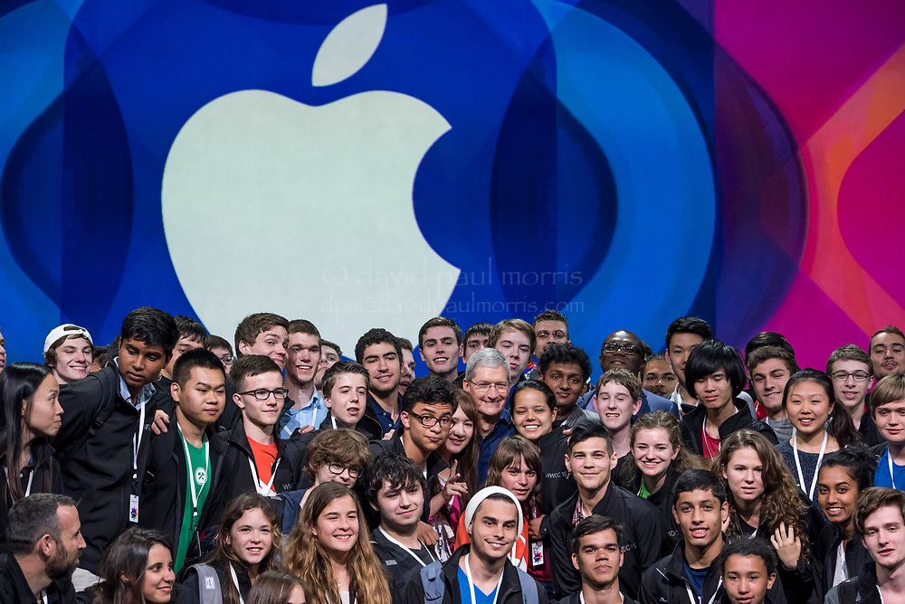 Tim Cook, chief executive officer of Apple Inc., poses for a photograph with high school students during the Apple World Wide Developers Conference (WWDC) in San Francisco, California, U.S., on Monday, June 8, 2015. Apple Inc., the maker of iPhones and iPads, will introduce software improvements for its computer and mobile devices as well as reveal new updates, including the introduction of a revamped streaming music service. Photographer: David Paul Morris/Bloomberg *** Local Caption *** Tim Cook
