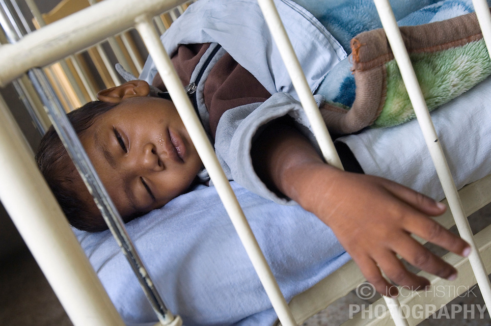 RAWALPINDI, PAKISTAN - NOV-01-2006 - An orphan sleeps at the St. Joseph Hospice Orphange. The hospice was started by Father Francis O'Leary, an Irish missionary, in 1964. Franciscan nuns of the Missionaries of Mary, run the hospice and have a fully trained staff of 26 Pakistani nurses aides and volunteer doctors. The hospice, orphanage and free clinic has 60 beds for resident patients and treats 80-90 out patients daily.  All medical services are free of charge to resident patients at St. Joseph's, regardless of the cost, duration or type of treatment required. The hospice is supported solely by donations.  (PHOTO © JOCK FISTICK)