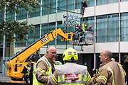 Specialist police officers use a cherry picker to approach two climate activists from HS2 Rebellion who scaled the Marsh insurers building in the City of London in protest against the HS2 high-speed rail project on 2nd September 2021 in London, United Kingdom. Marsh JLT Specialty are the main insurers for HS2.