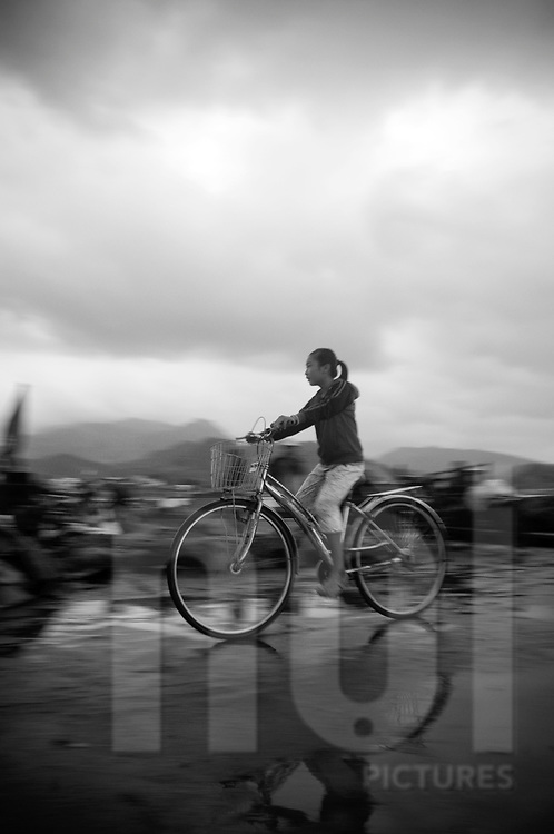 After rain, a girl rides bicylce. Region Nha Trang, Khanh Hoa, Viet Nam, Asia.