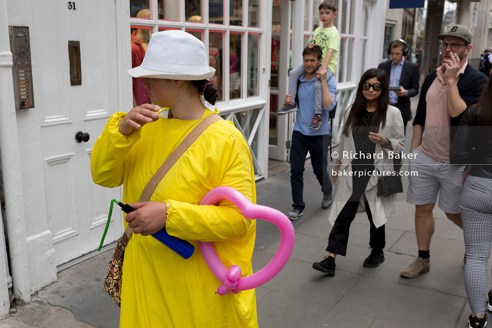 A woman wearing yellow carries a pink balloon in the crook of her arm, on 30th May 2019, in London, England.