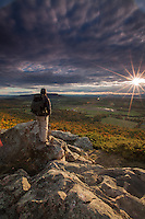 Hiker, Mark Waslick admires the sunset view from the summit of buck mtn. outside Vergennes, Vermont.