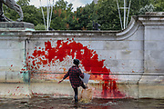 """An Animal and climate activist from the Animal Rebellion activists group throws a red colour on the fountain outside Buckingham Palace on Thursday, Aug 26, 2021 - signifying as their statement said """"its' demonstrable role in hunting and animal agriculture"""". (VX Photo/ Vudi Xhymshiti)"""
