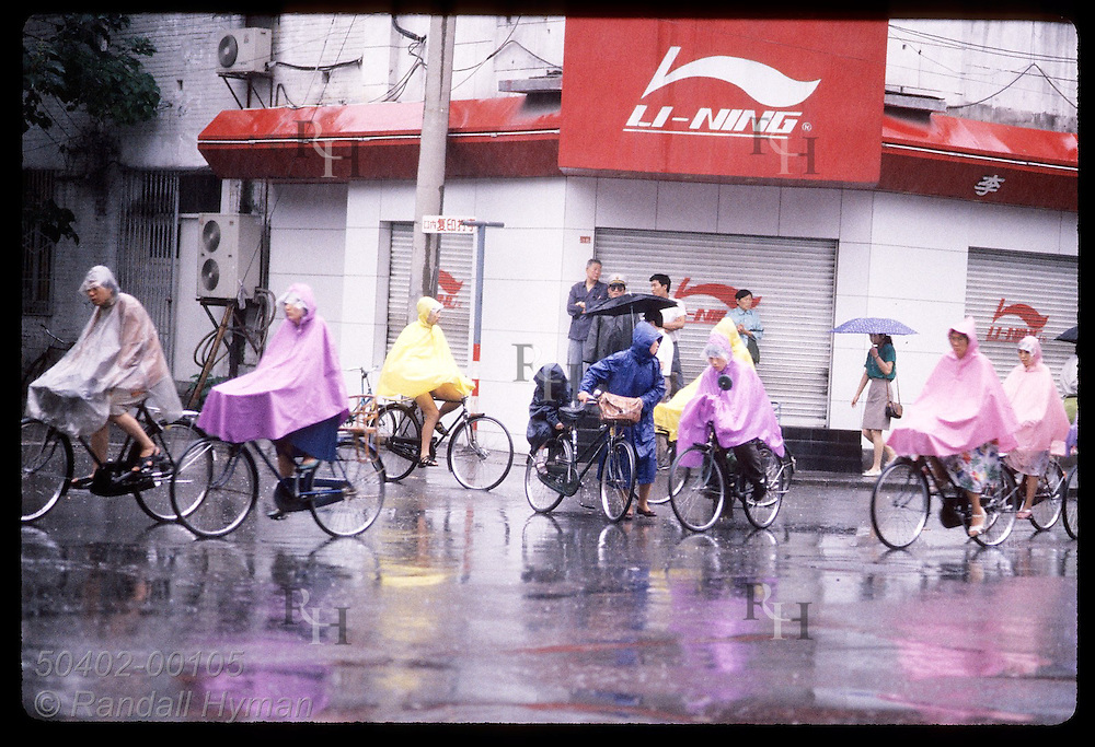 Bicycle commuters in rain ponchos stream thru intersection amid downpour of stormy morn; Beijing China