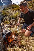 Tramper Geoff Spearpoint boils billy on wood fire during lunch break , Mathias river, Canterbury, New Zealand.
