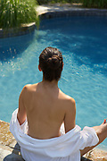 Back view of woman sitting on the edge of a free form swimming pool with a robe covering lower part of her back