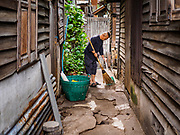 12 JUNE 2017 - BANGKOK, THAILAND: TAWATCHAI VORAMAHAKUN, a community historian and leader in the Pom Mahakan slum, sweeps up between homes. Bangkok city officials are expected to tear the structure down in coming weeks. The final evictions of the remaining families in Pom Mahakan, a slum community in a 19th century fort in Bangkok, have started. City officials are moving the residents out of the fort. NGOs and historic preservation organizations protested the city's action but city officials did not relent and started evicting the remaining families in early March.             PHOTO BY JACK KURTZ