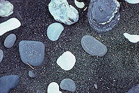 Smooth river stones in black sand