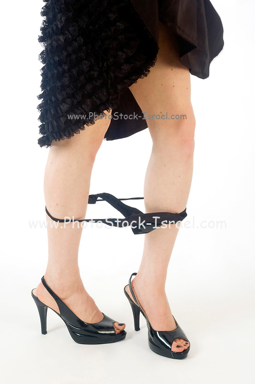 A young Caucasian female model of 26 with her Knickers around her ankles only her feet are displayed so there is only a hint to nudity white background