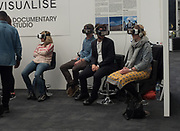 Exhibition visitors In a virtual environment called Birdlife. They are watching penguins in the Falklands. , Virtual Reality Show, Business Design Centre, Islington. London.  20 April 2017