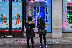 © Licensed to London News Pictures. 21/12/2020. LONDON, UK. People view the window decorations in Regent Street in the West End as Tier 4, Stay at Home, alert level restrictions are imposed on much of the UK to combat the ongoing coronavirus pandemic in the light of a recently discovered mutant strain that was discovered in the south east of England.  Photo credit: Stephen Chung/LNP