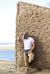 cowboy leaning against an adobe wall in New Mexico