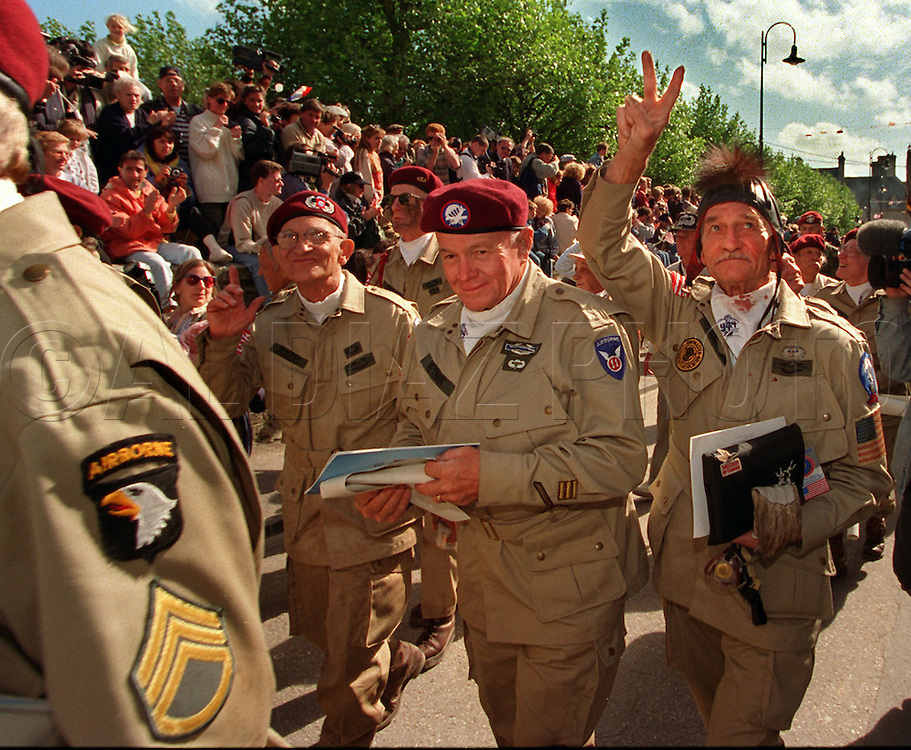 Airborne veterans D.L. Reyman, at center, and Elsworth Harger, flashing a victory sign, march into Ste. M`ere-Eglise after they parachuted in at the outskirts of town during ceremonies for the 50th Anniversary of D-Day on June 5th 1994