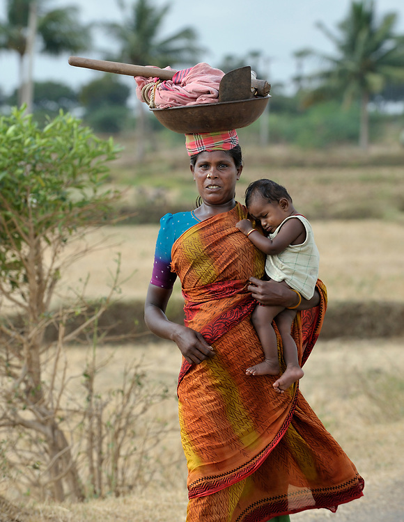 Carrying a child, a woman walks to work her farm field in Anaikulam, a small village in the state of Tamil Nadu in southern India.