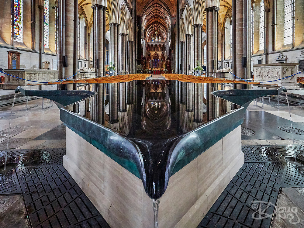 The Font at Salisbury Cathedral by William Pye with Gothic columns and stained glass windows in the background.<br /> <br /> Salisbury, Wiltshire, UK