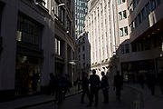 Reflected light and City workers in silhouette in the City of London, England, United Kingdom.