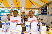 African American kids handing out fruit bars. Special Olympics U of M Bierman Athletic Complex. Minneapolis Minnesota USA