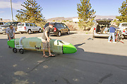 Een team rijdt de rug-aan-rugtandem over de parkeerplaats. Bij het Super 8 Hotel in Battle Mountain werken verschillende teams aan hun fietsen.<br />