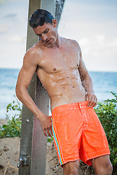 sexy muscular man in an outdoor shower at the beach