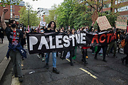 Protesters walk behind a Palestine Action banner during a Free Palestine SOS Colombia march in solidarity with the Palestinian and Colombian peoples from the Colombian embassy to the Israeli embassy on 15th May 2021 in London, United Kingdom. Speakers at a rally before the march, which took place on Nakba Day, highlighted human rights abuses being directed against Palestinians in Israel and the Occupied Territories, in particular attempts at forced displacements in Sheikh Jarrah in East Jerusalem, and also in Colombia, where peaceful demonstrators and human rights defenders have been killed and subjected to repression, detention and torture.