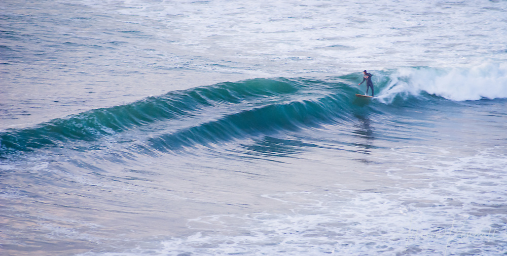Off the coast of Big Sur, a surfer catches a double wave as the sun sets