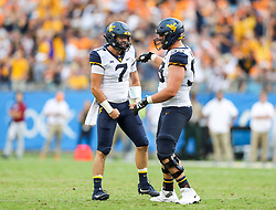 Sep 1, 2018; Charlotte, NC, USA; West Virginia Mountaineers quarterback Will Grier (7) celebrates with West Virginia Mountaineers offensive lineman Colton McKivitz (53) after throwing a touchdown pass during the third quarter aTennessee Volunteers at Bank of America Stadium. Mandatory Credit: Ben Queen-USA TODAY Sports