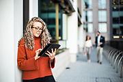 Woman working on a smart device stood outside a corporate office in St Helier, Jersey, Channel Islands