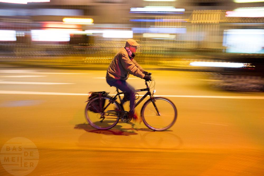 In Eindhoven fietst een oudere man 's avonds met de verlichting door de stad.<br /> <br /> In Eindhoven an eldery man is cycling in the evening.