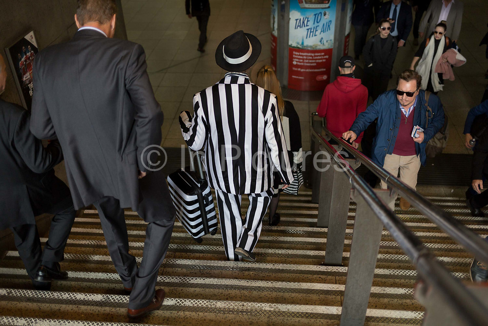 A man wearing a striped suit descends the steps of Westminster Underground Station, on 16th October 2018, in London, England.