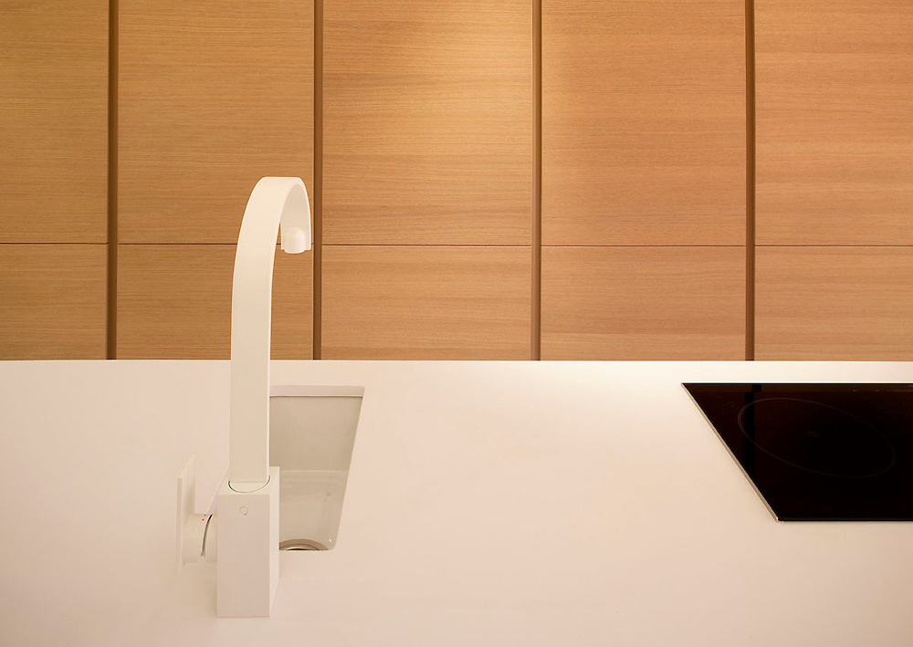 white kitchen tap and sink with wooden units in background