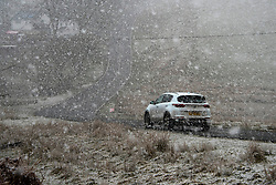 © Licensed to London News Pictures. 11/04/2021. Builth Wells, Powys, Wales, UK. A motorist drives along the B4520 (Brecon road) in an unseasonal wintry landscape on the Mynydd Epynt range near Builth Wells in Powys, Wales, UK. Photo credit: Graham M. Lawrence/LNP